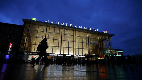People are silhouetted as they walk past the main railway station in Cologne, Germany © Wolfgang Rattay