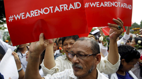 People hold placards during a rally at the scene of Thursday's gun and bomb attack in central Jakarta, Indonesia. © Garry Lotulung