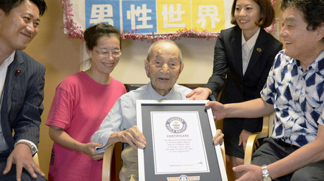 Japanese Yasutaro Koide (C), 112, receives the Guinness World Records certificate as he is formally recognized as the world's oldest man, at a nursing home in Nagoya, central Japan © Kyodo