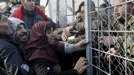 Syrian refugees struggle to enter Macedonia through a narrow border crossing as Macedonian policemen try to shut a metal gate near to the Greek village of Idomeni. © Yannis Behrakis