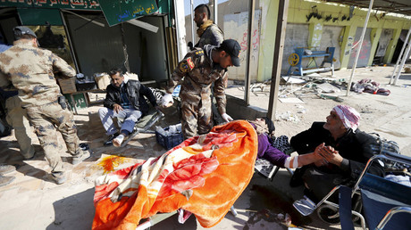 Iraqi security forces help wounded civilians as they flee the violence in the city of Ramadi, Iraq, January 16, 2016. © Thaier Al-Sudani