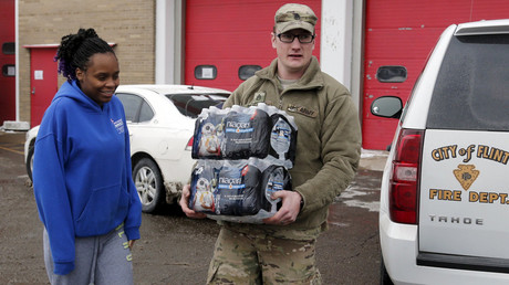 Michigan National Guard Staff Sergeant William Phillips (R) assists a Flint resident with bottled water at a fire station in Flint, Michigan January 13, 2016. © Rebecca Cook