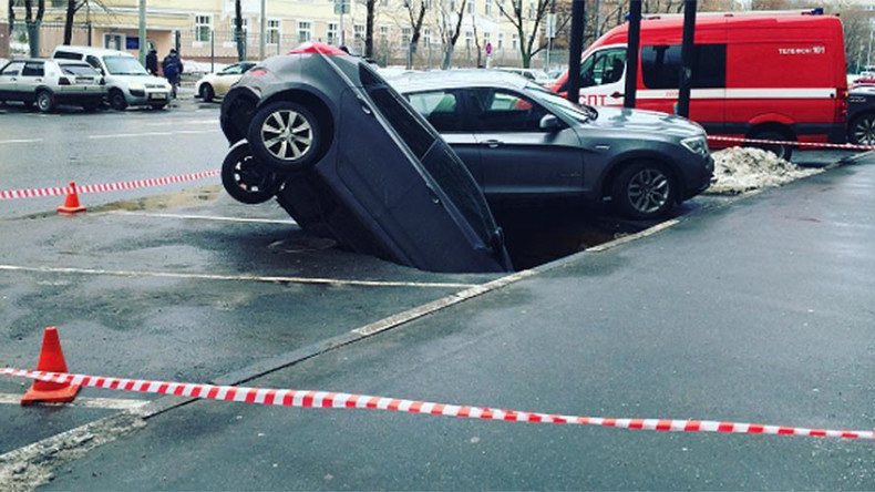 Forgot to pay the fee? Moscow paid parking spot cracks open, swallows 2 cars (PHOTOS, VIDEO)