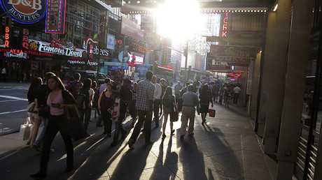 People walk along 42nd Street as the sun sets on Times Square in New York © Gary Hershorn