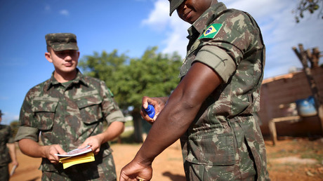 A health agent uses pesticide next to Brazilian soldiers as they conduct an inspection for the Aedes aegypti mosquito © Adriano Machado