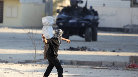 A protester throws a stone at a riot police armoured personnel carrier during anti-government clashes in the village of Sitra, south of Manama, February 14, 2016.© Hamad I Mohammed