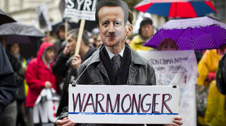 File photo: A man wearing a British Prime Minister David Cameron mask holds a sign which reads