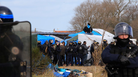 French riot police secure the area as a migrant sits on his makeshift shelter during the partial dismantlement of the camp for migrants called the
