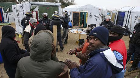 French CRS riot police secure the area near makeshift shelters during the partial dismantelment of the camp for migrants called the
