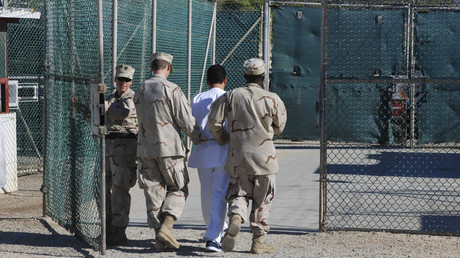 File photo: US Navy guards escort a detainee through Camp Delta at Guantanamo Bay naval base © Reuters