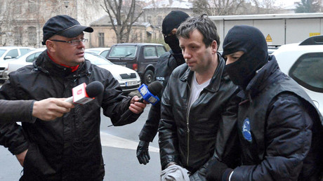 Marcel Lazar Lehel, aka Guccifer, is escorted by masked policemen in Bucharest after his arrest in 2014. © Silviu Matei
