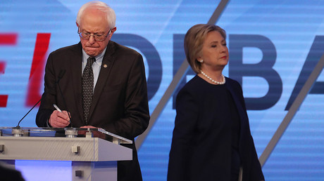 Democratic U.S. presidential candidate Senator Bernie Sanders writes on his notes as his rival Hillary Clinton walks behind him during a commercial break at the Univision News and Washington Post Democratic U.S. presidential candidates debate in Kendall, Florida March 9, 2016 © Carlo Allegri