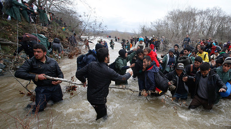 Migrants wade across a river near the Greek-Macedonian border, west of the the village of Idomeni, Greece, March 14, 2016 © Stoyan Nenov