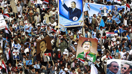 Yemenis hold placards bearing portraits of former president Ali Abdullah Saleh during a protest against the Saudi-led coalition, on March 26, 2016, in the Yemeni capital Sanaa. © Mohammed Huwais