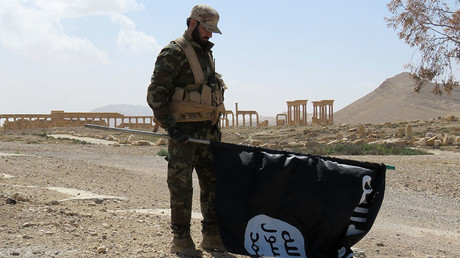 A member of the Syrian pro-government forces carries an Islamic State (IS) group flag as he stands on a street in the ancient city of Palmyra on March 27, 2016, after troops recaptured the city from IS jihadists. © AFP