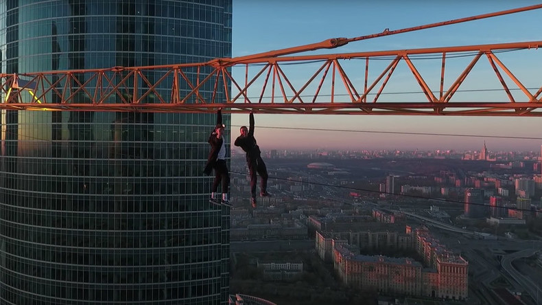Just crane crazy! Fearless daredevils hang over Moscow with one arm (DRONE VIDEO)