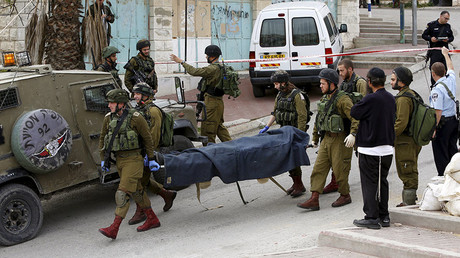Israeli soldiers carry the dead body of one of two Palestinians, whom the Israeli military said were shot dead by Israeli troops after they attacked an Israeli soldier, in Tal Rumaida in the West Bank city of Hebron March 24, 2016. © Mussa Qawasma