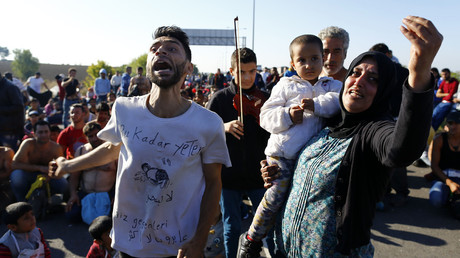 A woman holding a child reacts as Turkish police and gendarmes block migrants on a highway near Edirne, Turkey. File photo. © Osman Orsal