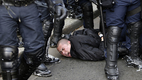 Anti-riot police officers arrest a man during clashes within a demonstration of high school students protesting against the government's planned labour reform, on April 5, 2016 in eastern Paris. © Kenzo Tribouilard