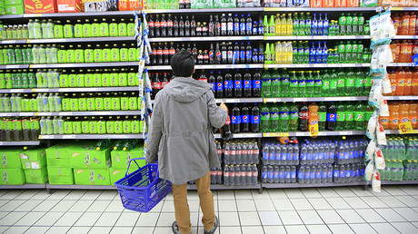 A consumer chooses soft drinks at a supermarket in Shanghai, China. © Aly Song