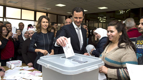 Syria's President Bashar al-Assad (C) casts his vote next to his wife Asma (centre left) inside a polling station during parliamentary elections in Damascus, Syria, in this handout picture provided by SANA on April 13, 2016. © SANA