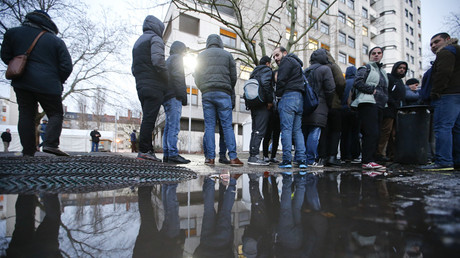 Migrants are reflected in a puddle as they queue in front of the compound of the Berlin Office of Health and Social Affairs (LAGESO) for their registration process, early morning in Berlin, Germany © Fabrizio Bensch