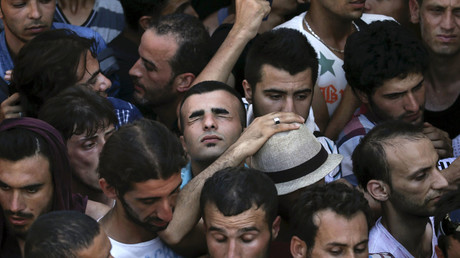 A Syrian refugee tries to catch his breath as he stands in a crowded line to get registered in the national stadium of the Greek island of Kos, August 12, 2015. © Alkis Konstantinidis