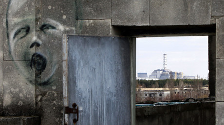 The sarcophagus covering the damaged fourth reactor at the Chernobyl nuclear power plant is seen behind a building decorated with a graffiti in the abandoned city of Prypiat. © Gleb Garanich