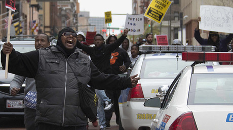 Demonstrators march through the streets protesting the death Freddie Gray, an African American man who died of spinal cord injuries in police custody, in Baltimore, Maryland, April 25, 2015. © Jim Watson