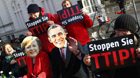 Protesters wear masks of U.S. President Barack Obama and German Chancellor Angela Merkel as they demonstrate against Transatlantic Trade and Investment Partnership (TTIP) free trade agreement before the opening ceremony of the Hannover Messe in Hanover, Germany April 24, 2016. © Kai Pfaffenbach