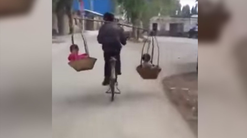 Dexterous dad carries children in baskets while balancing on bike (VIDEO)