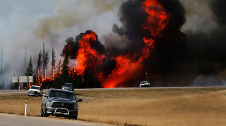 Smoke and flames from the wildfires erupt behind cars on the highway near Fort McMurray, Alberta, Canada, May 7, 2016. © Mark Blinch / Reuters