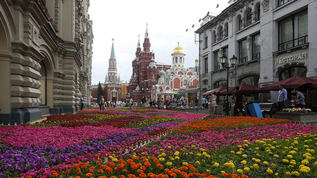 People walk past flowers located near GUM department store, Red Square and the Kremlin in central Moscow © Sergei Karpukhin