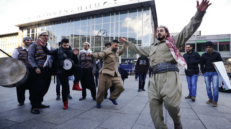 Migrants dance in front of the railway station during the