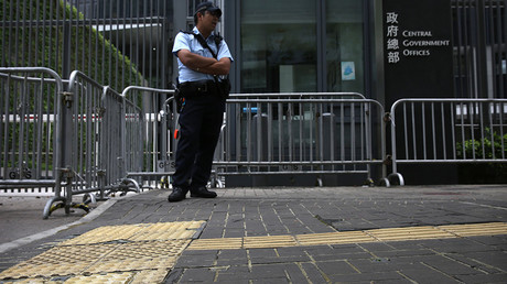 A policeman stands on pavement reinforced with glue to prevent the bricks from being dug up and used as projectiles during expected protests outside the central government offices in downtown Hong Kong on May 16, 2016 © Isaac Lawrence