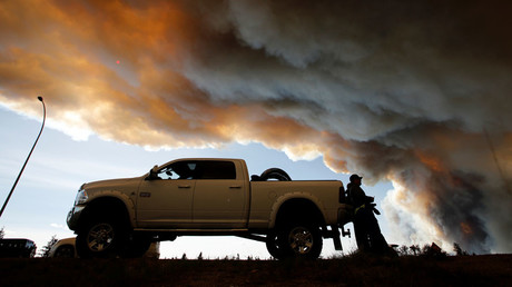 People wait at a roadblock as smoke rises from wildfires near Fort McMurray, Alberta, Canada © Chris Wattie