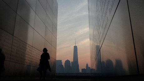A woman looks at names of victims on the wall of the 9/11 Empty Sky memorial at sunrise across from New York's Lower Manhattan and One World Trade Center in Liberty State Park in Jersey City, New Jersey © Gary Hershorn