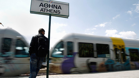 A man stands as a train passes in front of him at a central train station in Athens © John Kolesidis