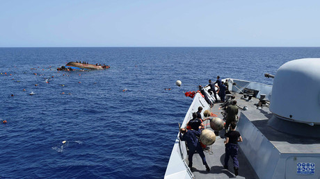 Migrants are rescued from a capsized boat during a rescue operation by Italian navy ships