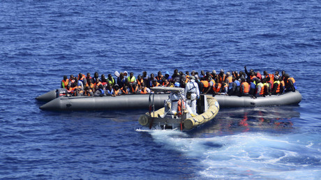 Migrants sit in their boat during a rescue operation by Italian Navy vessels off the coast of Sicily © Marina Militare