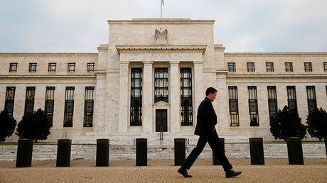 A man walks past the Federal Reserve Bank in Washington, D.C. © Kevin Lamarque