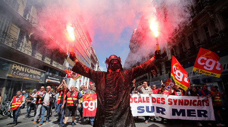 An Arcelor Mittal steel worker, dressed in a protective work suit with a mask of Darth Vader from Star Wars, holds flares during a demonstration in protest of the government's proposed labour law reforms in Marseille, France, June 2, 2016 © Jean-Paul Pelissier