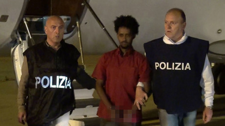 Medhanie Yehdego Mered, 35, an Eritrean suspected of controlling a migrant trafficking network, escorted by policemen upon his extradition from Sudan to Italy late on June 6, 2016. © Polizia di Stato