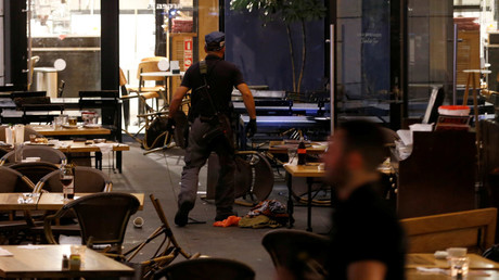 An Israeli policeman searches a restaurant following a shooting attack in the center of Tel Aviv June 8, 2016. © Baz Ratner