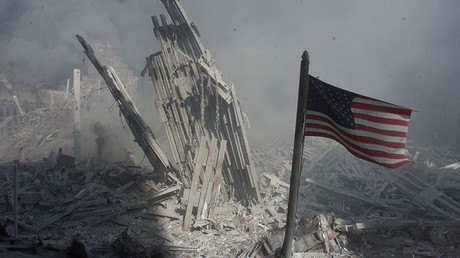An American flag flies near the base of the destroyed World Trade