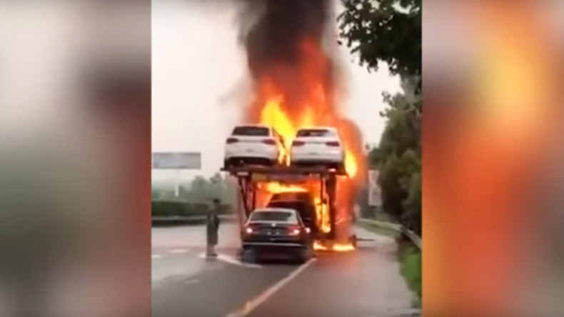 Driver reverses new car off of blazing transporter (VIDEO)