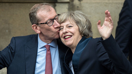 Britain's new Conservative Party leader Theresa May (R) receives a kiss from her husband Philip John May (L), after speaking to members of the media at The St Stephen's entrance to the Palace of Westminster in London on July 11, 2016. © Chris Ratcliff