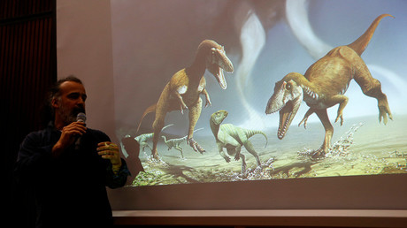 Argentine paleontologist Sebastian Apesteguia speaks next to a screen showing two Cretaceous Period predatory dinosaurs (L and R) named Gualicho in northern Patagonia 90 million years ago in Buenos Aires, Argentina, July 13, 2016. © Enrique Marcarian