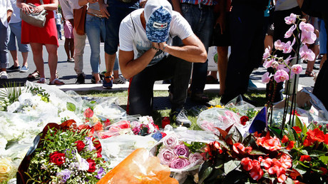 A man reacts near bouquets of flowers as people pay tribute near the scene where a truck ran into a crowd at high speed killing scores and injuring more who were celebrating the Bastille Day national holiday, in Nice, France, July 15, 2016. © Pascal Rossignol