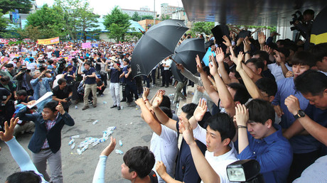 South Korean officials try to protect Prime Minister Hwang Kyo-Ahn from water bottles and eggs being thrown by angry protesters as he visits Seongju on July 15, 2016. © Yonhap